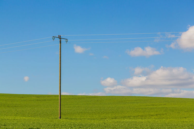 Sky Cable Landscape Land Electricity  Field Technology Grass Cloud - Sky Power Line  Environment Green Color Tranquility Nature Day Scenics - Nature No People Beauty In Nature Tranquil Scene Plant Power Supply Outdoors Parallel Electrical Equipment Electricity  Simplicity Simple Photography