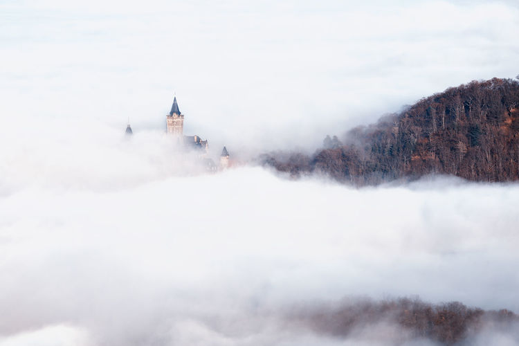 View of church on mountain amidst cloud