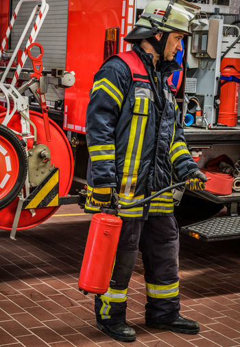 Full length of firefighter holding cylinder
