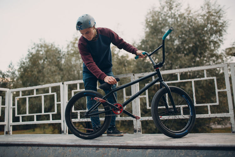Man with bicycle by railing outdoors