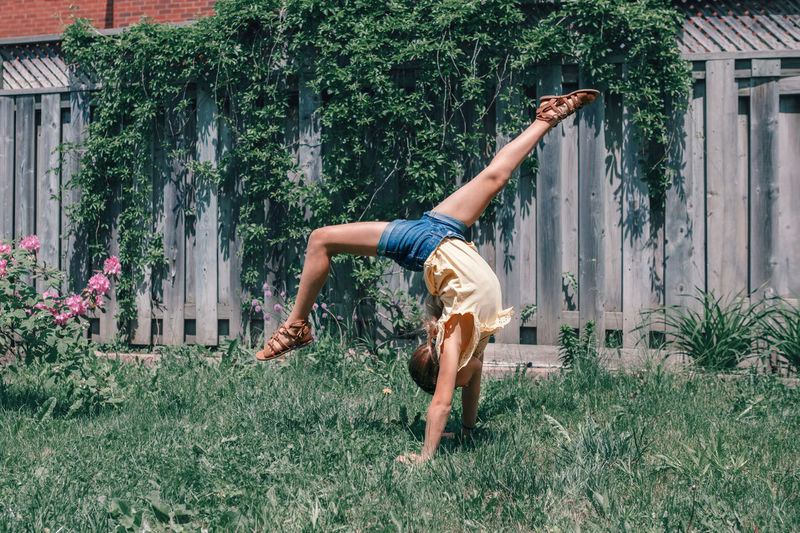 Girl balancing on handstand at yard against fence