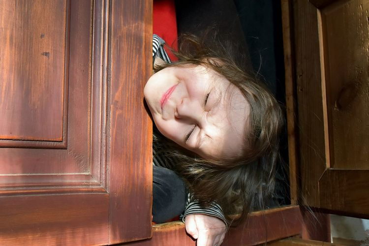 Cute Girl With Eyes Closed In Cabinet
