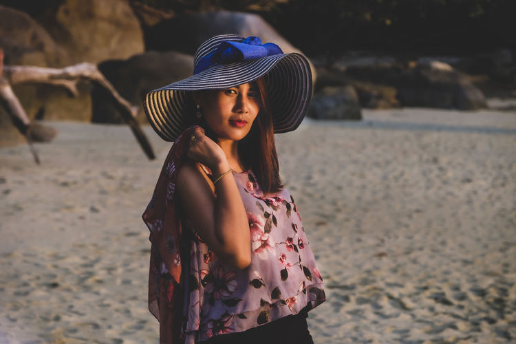 Young woman wearing hat while standing on beach
