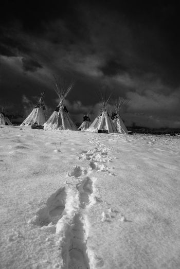 Footprints Leading Towards Teepee Tents On Snow Covered Field
