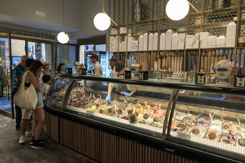 """Rome, Italy - June 11, 2018: Gelateria """"Della Palma"""" is a well-known café and pastry shop, and reportedly one the oldest ice cream parlor in Rome, Italy. Colourful interior, people, ice cream and gelato. Coliseum Quirinale Rome Viminale Europe Fori Romani Italy Trevi"""