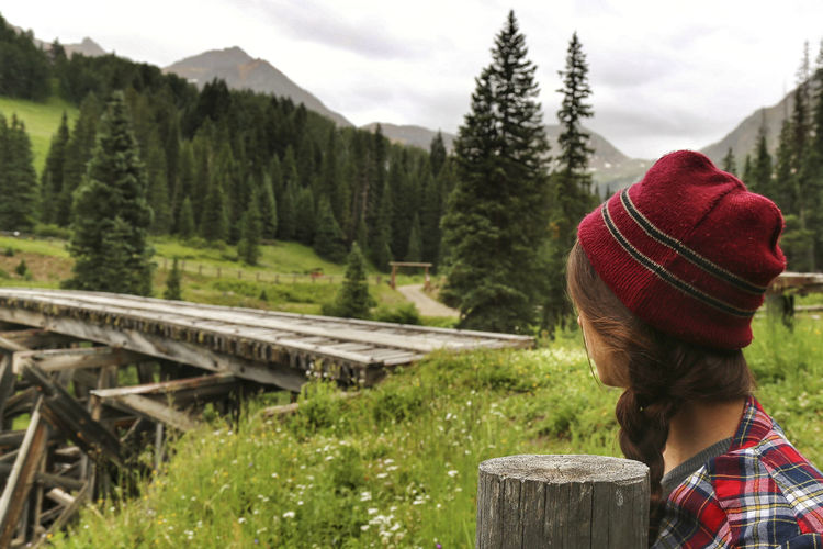A young woman stands by a bridge on a beautiful rainy day in the mountains of Colorado Cloudy Day Colorado Hat Red San Juan Telluride Beanie Beauty In Nature Day Flannel Shirt Forest Kerry Estey Keith Leisure Activity Lifestyles Mountain Nature One Person Outdoors Real People Rear View Sky Tree Trestle Warm Clothing Women