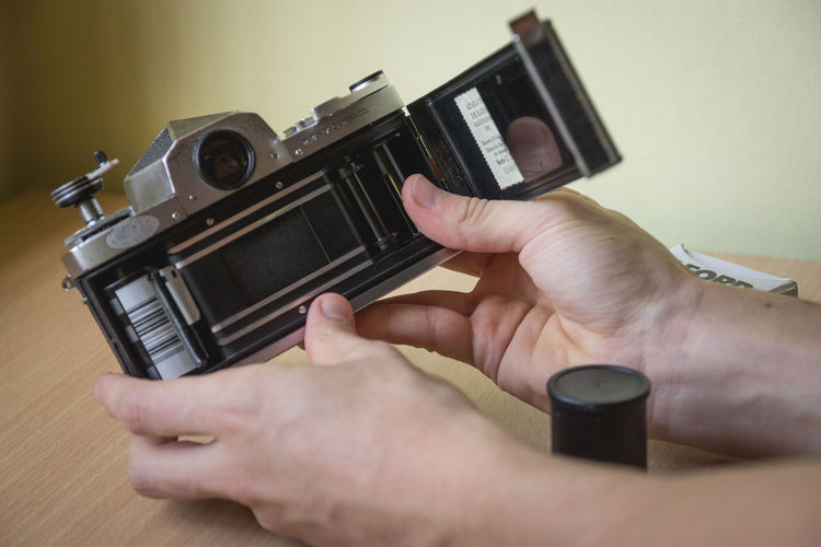 Cropped image of hand holding old-fashioned camera at table