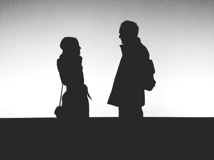 Silhouette people standing against white background