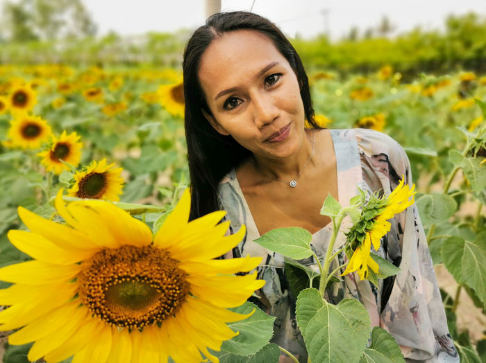 Portrait of woman with red sunflower
