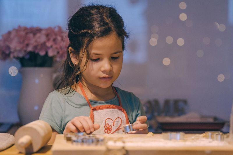 Close-up of girl making cookies on table at home