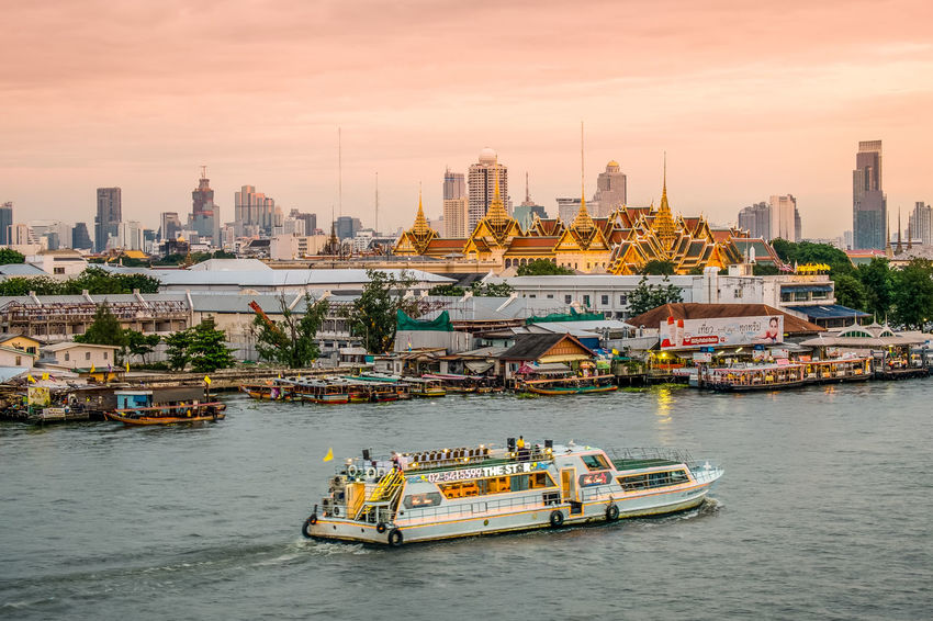 Grand Palace at Bangkok, Thailand Architecture Boat City City Life Cityscape Cloud - Sky Evening Sky Harbor Mode Of Transport Nautical Vessel River Sailing Sky Sunset Thailand Transportation Travel Destinations Urban Skyline Water Waterfront