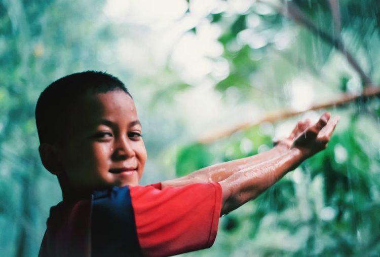 Portrait of happy boy looking away outdoors