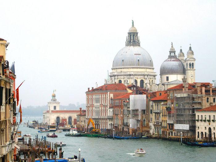 Santa Maria Della Salute By Venetian Lagoon Seen From Accademia Bridge Against Sky