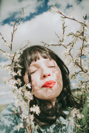 Portrait of girl with plants against trees