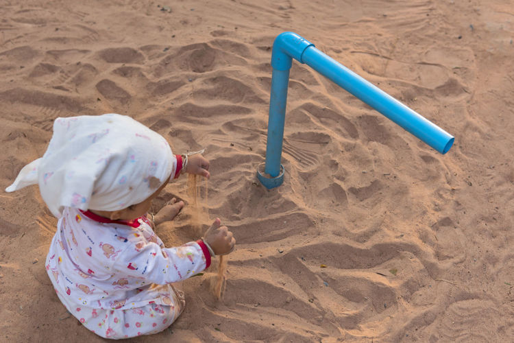 High angle view of girl playing with toy on sand