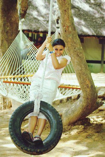 Portrait Of Happy Girl On Tire Swing By Hammock Over Field
