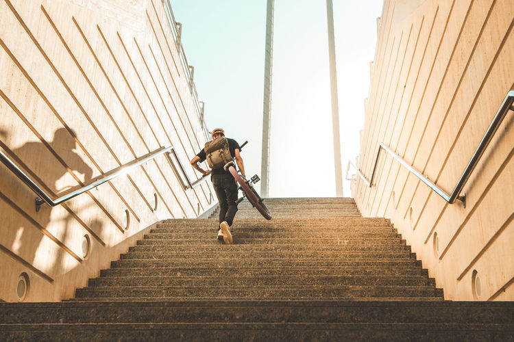 Low angle view of man walking on staircase