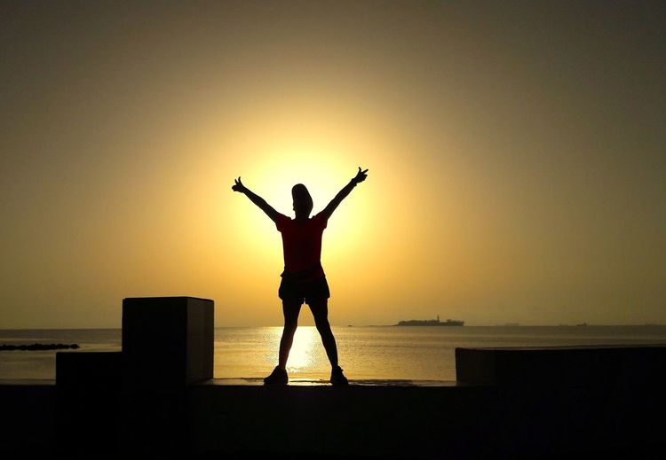 Silhouette Woman With Arms Raised Standing On Retaining Wall Against Sea During Sunset