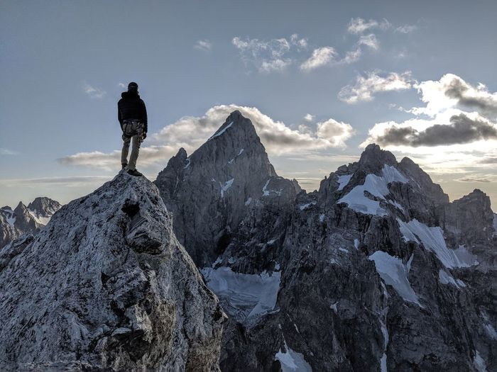 Rear view of man standing on snowcapped mountain against sky