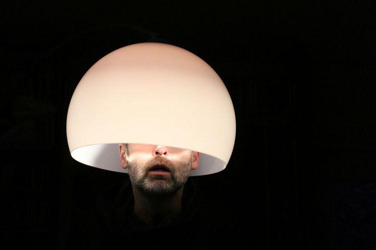 Mature man under illuminated lamp shade against black background