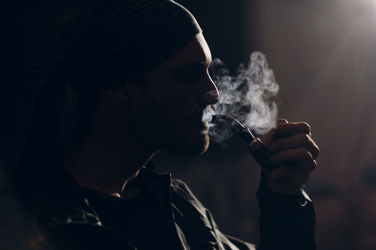 Rear view of man smoking cigarette