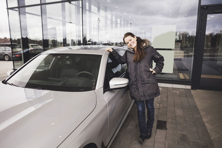 Full length of woman standing in car