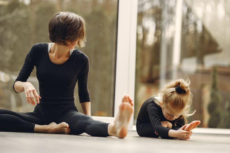 Unrecognizable female trainer teaching girl doing forward tilt on parquet