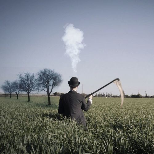 Rear View Of Man With Scythe On Field