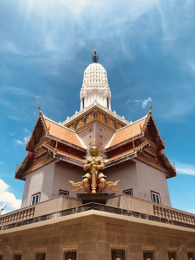 Low angle view of statue by temple against sky