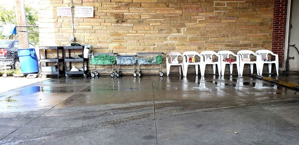 Empty chairs against wet wall in building