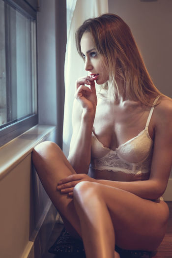 Seductive Woman Wearing Lingerie Looking Through Window At Home