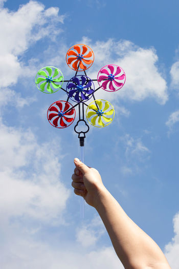 Low angle view of hand holding pinwheel toy against sky