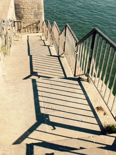 High Angle View Of Stairs By Sea On Sunny Day