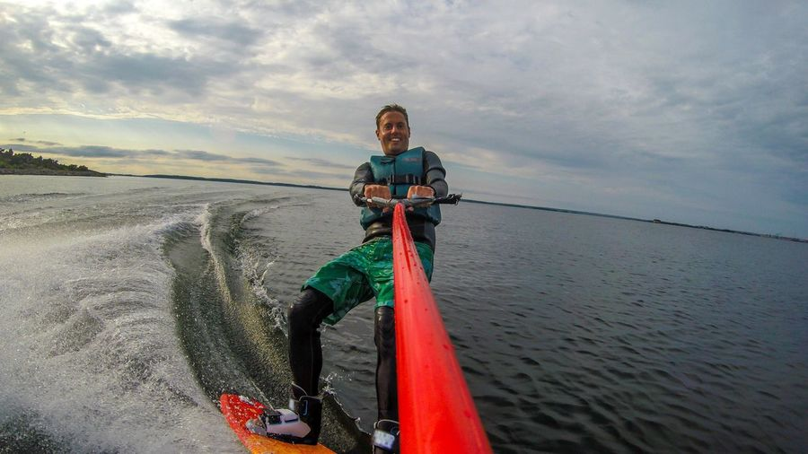 Man wakeboarding on sea against cloudy sky