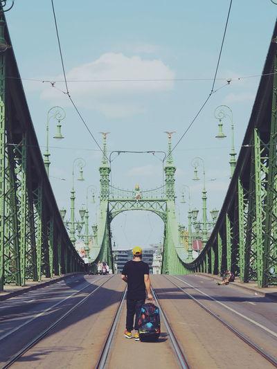 Rear view of man walking with luggage at liberty bridge