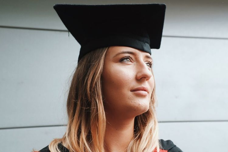 Close-up of young woman wearing mortarboard looking away while standing against wall