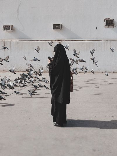 Woman standing in burka against pigeons on footpath