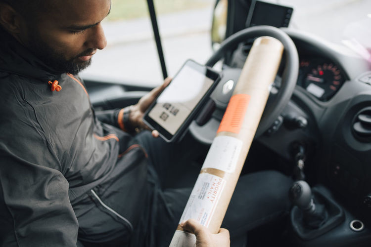Midsection of man using mobile phone in bus