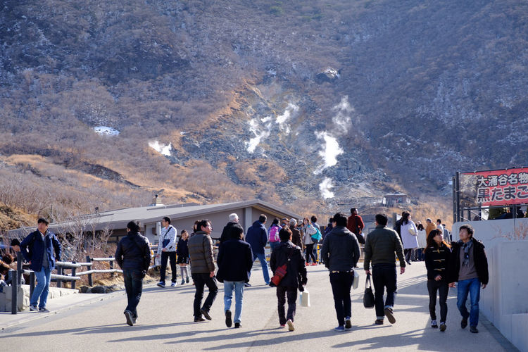 People walking on road against mountain