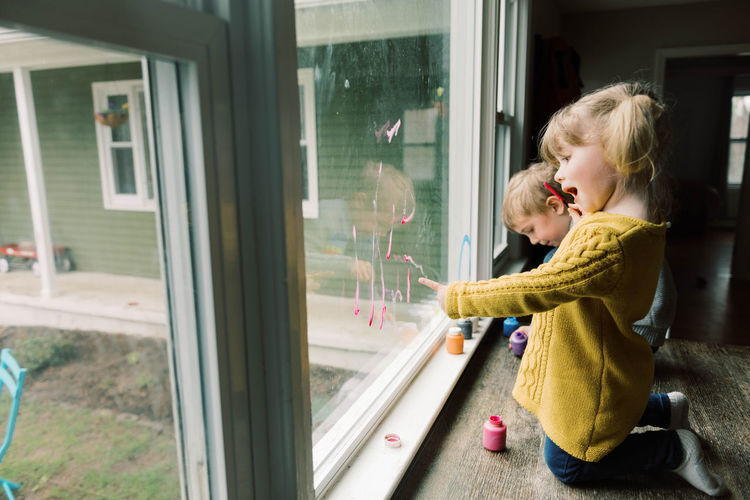 Side view of girl looking through window