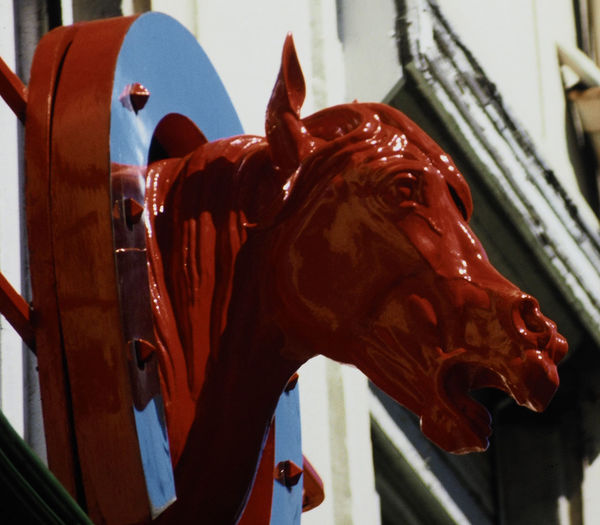 A vivid red horses head sign over a shop in Boulogne, France Horse Carousel Statue Day Sculpture Indoors  Close-up No People Shop Sign Animal Representation Wall Sign Horseshoe Sign Red Horses Head