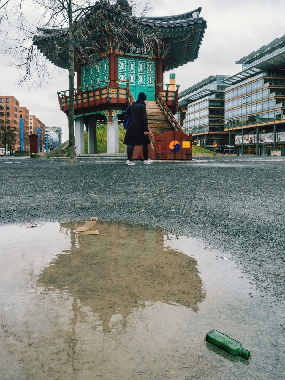 architecture, built structure, building exterior, real people, water, walking, men, outdoors, one person, day, standing, lifestyles, full length, puddle, sky, city, people