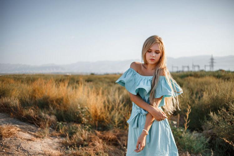 Teenage girl wearing dress standing on land against sky
