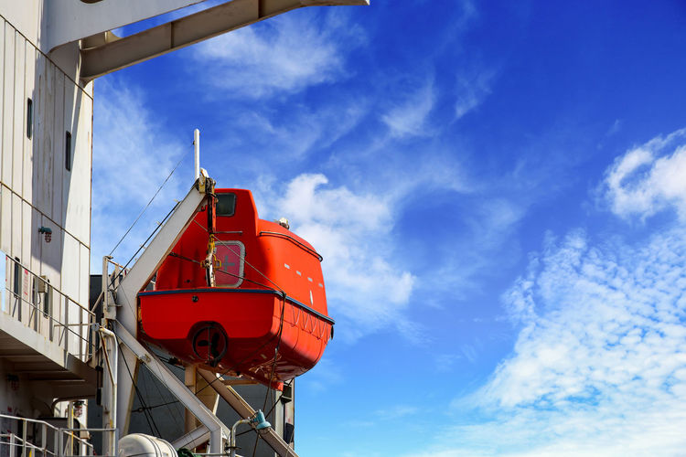 Low angle view of red ship against sky