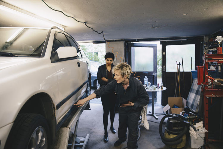 Female mechanic pointing while showing car to customer in auto repair shop