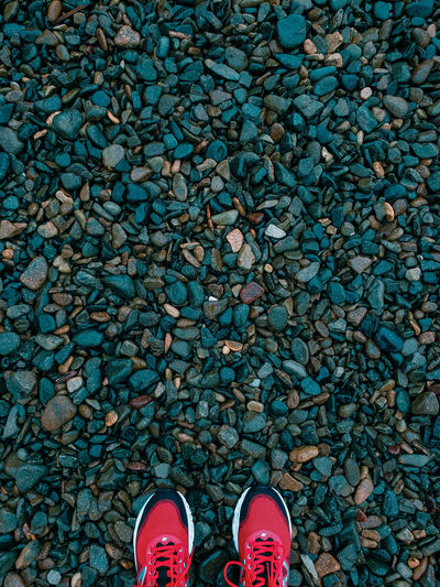 Low section of person standing on pebbles