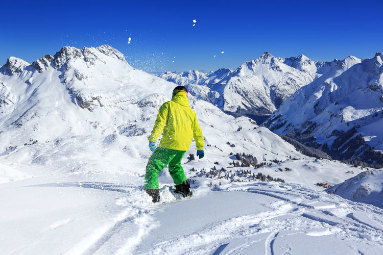 Rear View Of Man Snowboarding On Snowcapped Mountain Against Sky