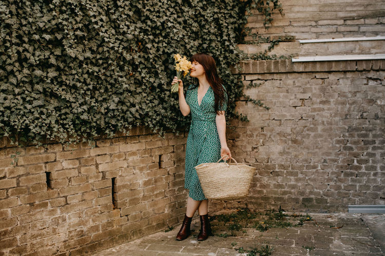 Full length of woman smelling flowers while standing against creeper wall