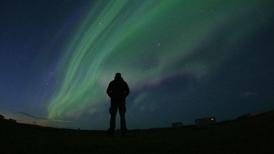Rear view of silhouette man standing against aurora polaris