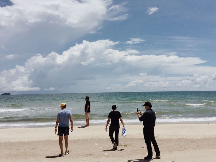 Rear view of people at beach against sky